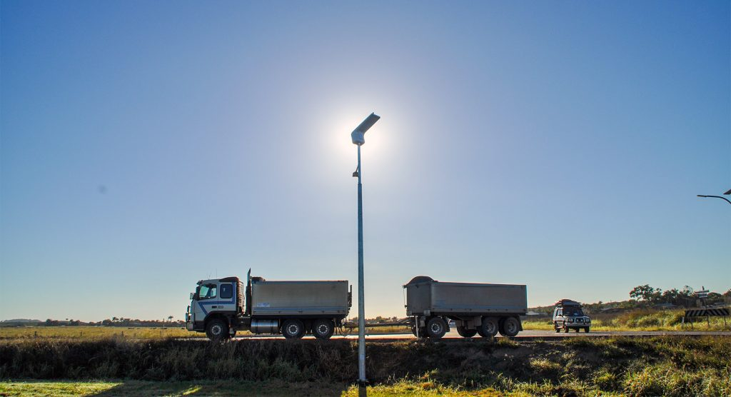 solar-powered commercial street light with sun behind it on the side of the road with dump trucks driving by